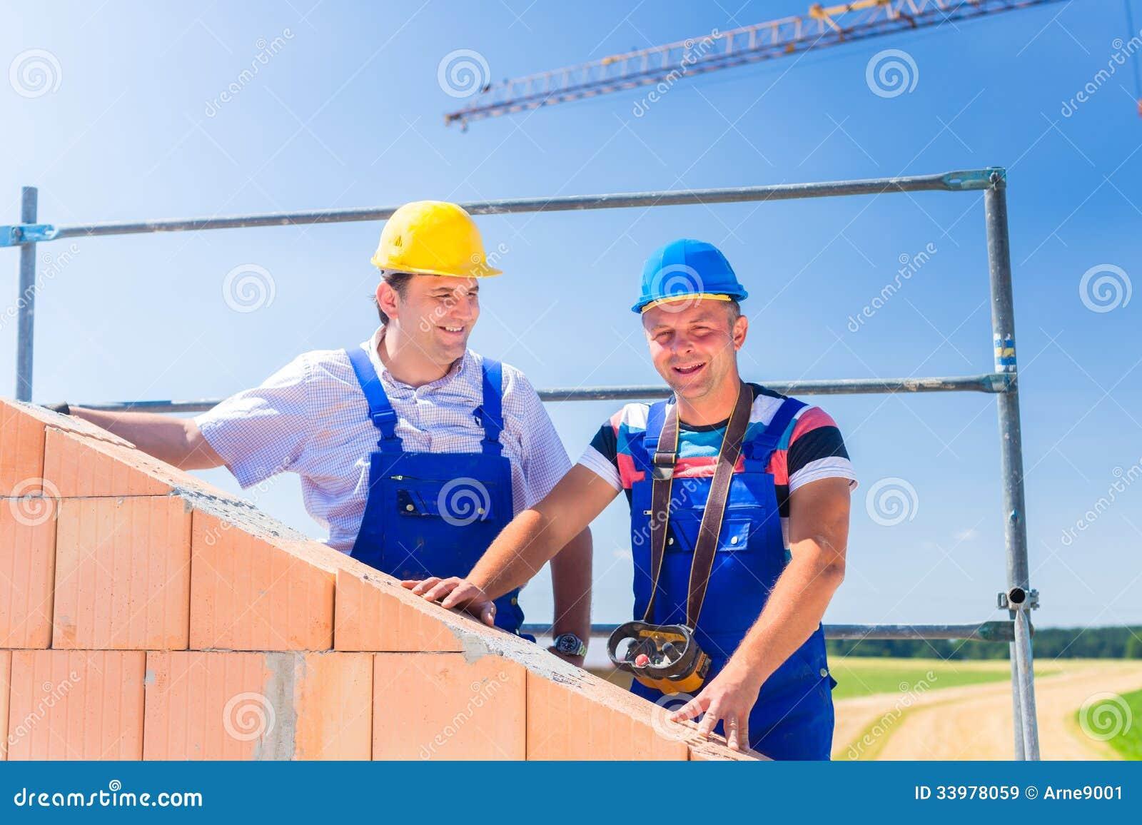 Lavoratori del cantiere che costruiscono casa con la gru for Casa del cantiere