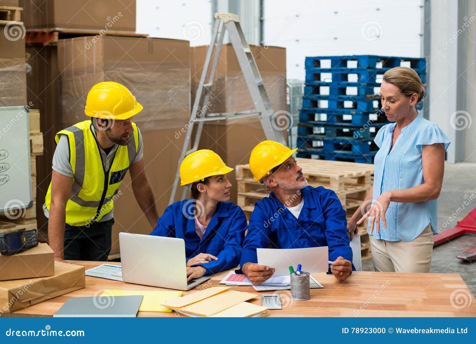 Lavoratori del magazzino che discutono con il responsabile