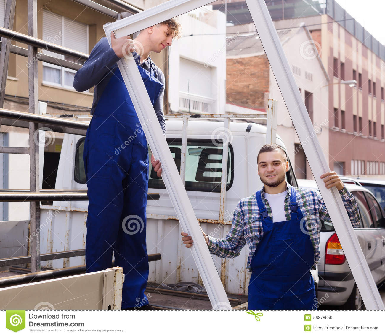Lavoratori in tuta che carica le strutture del PVC al camion
