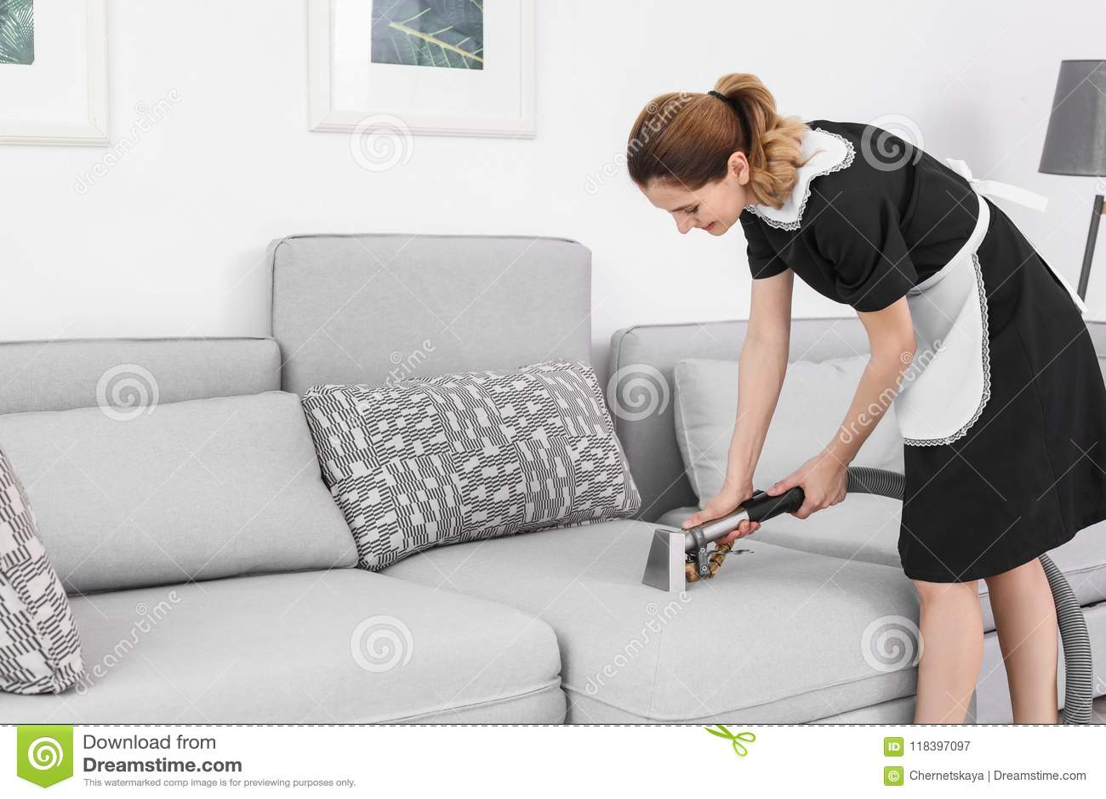 Lavoratrice che rimuove sporcizia dal sofà con l aspirapolvere professionale, all interno