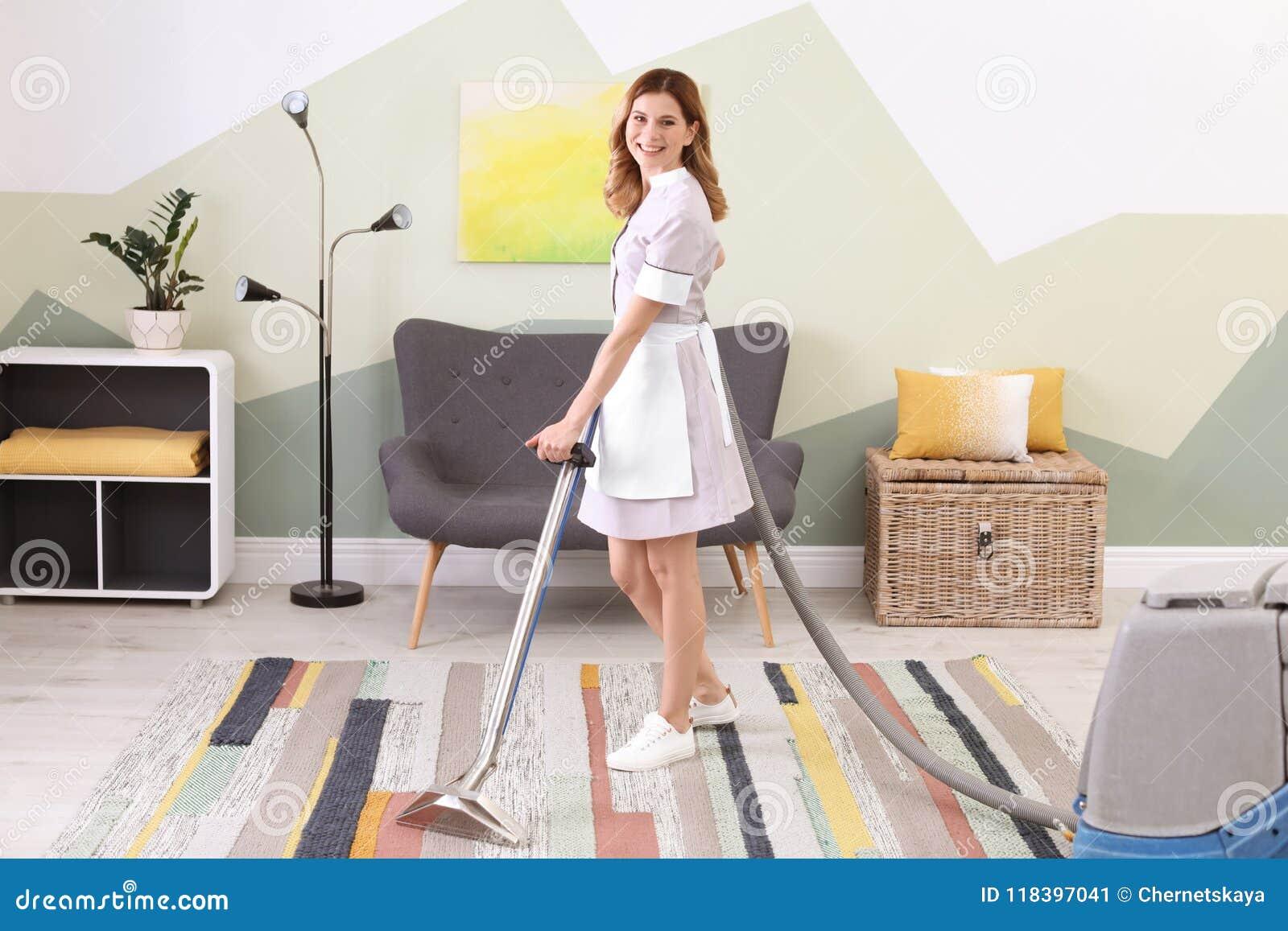 Lavoratrice che rimuove sporcizia dal tappeto con l aspirapolvere professionale, all interno