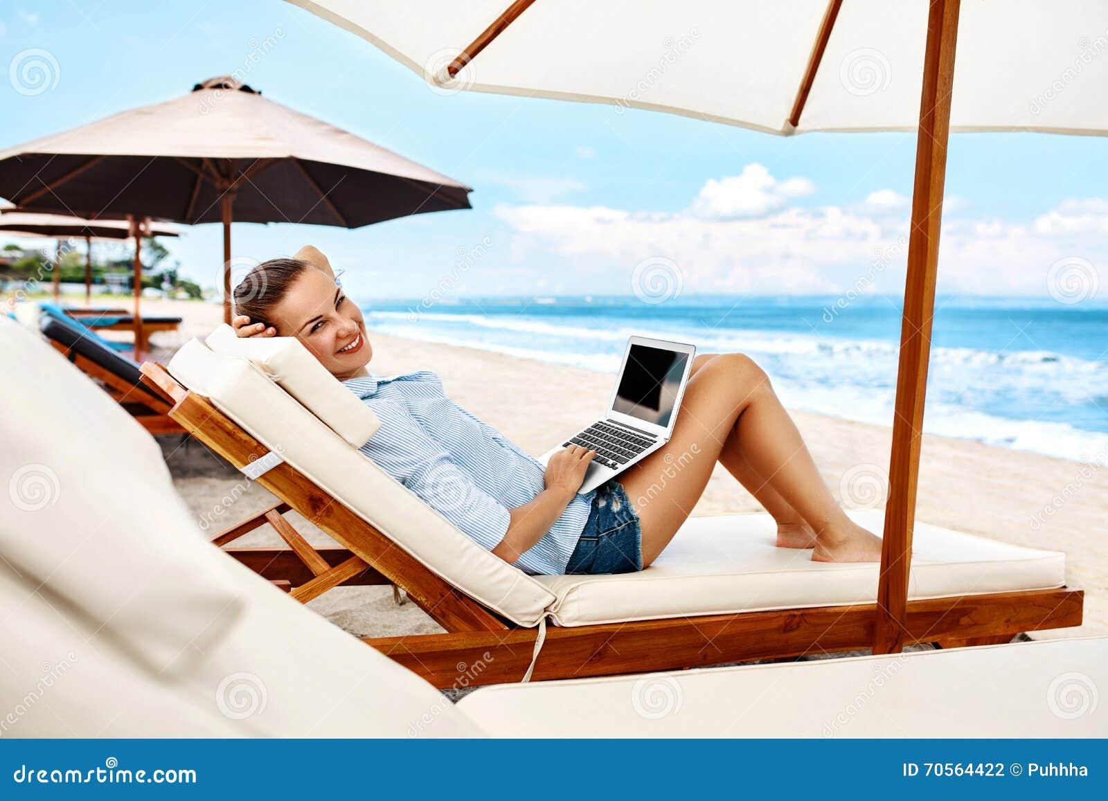 Lavoro di estate Donna che si rilassa facendo uso del computer sulla spiaggia freelance