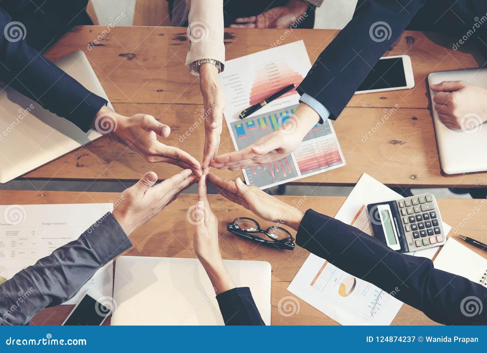 Lavoro di gruppo dei partner che si prende per mano insieme al successo Pila del gruppo di affari di mani per la stella sul proge