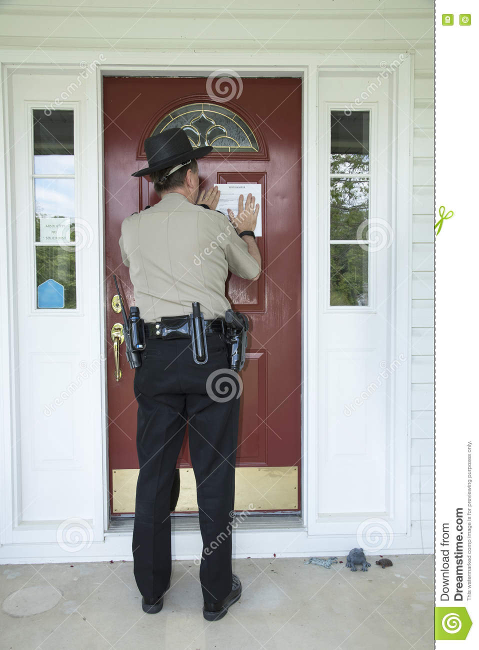 law enforcement officer posting an eviction notice stock photo