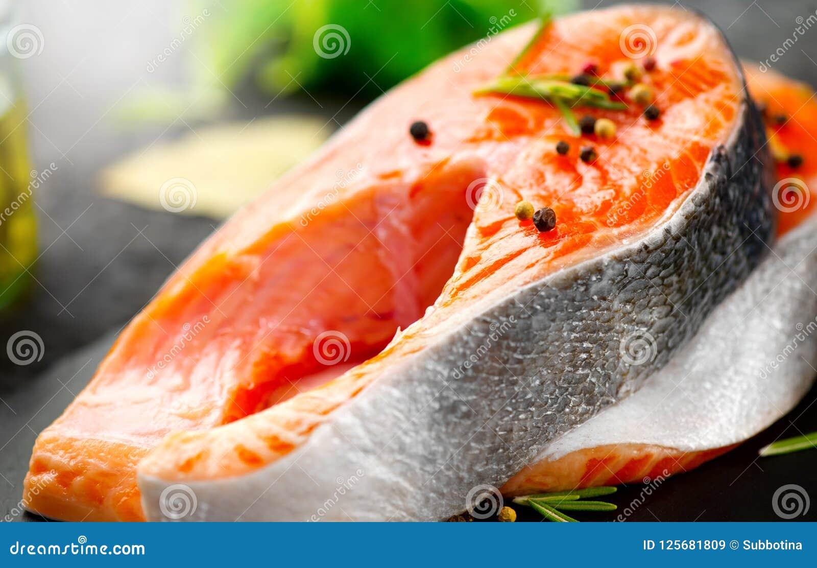 Lax Rå forellfiskbiff med örter och citronen på svart kritiserar bakgrund matlagning