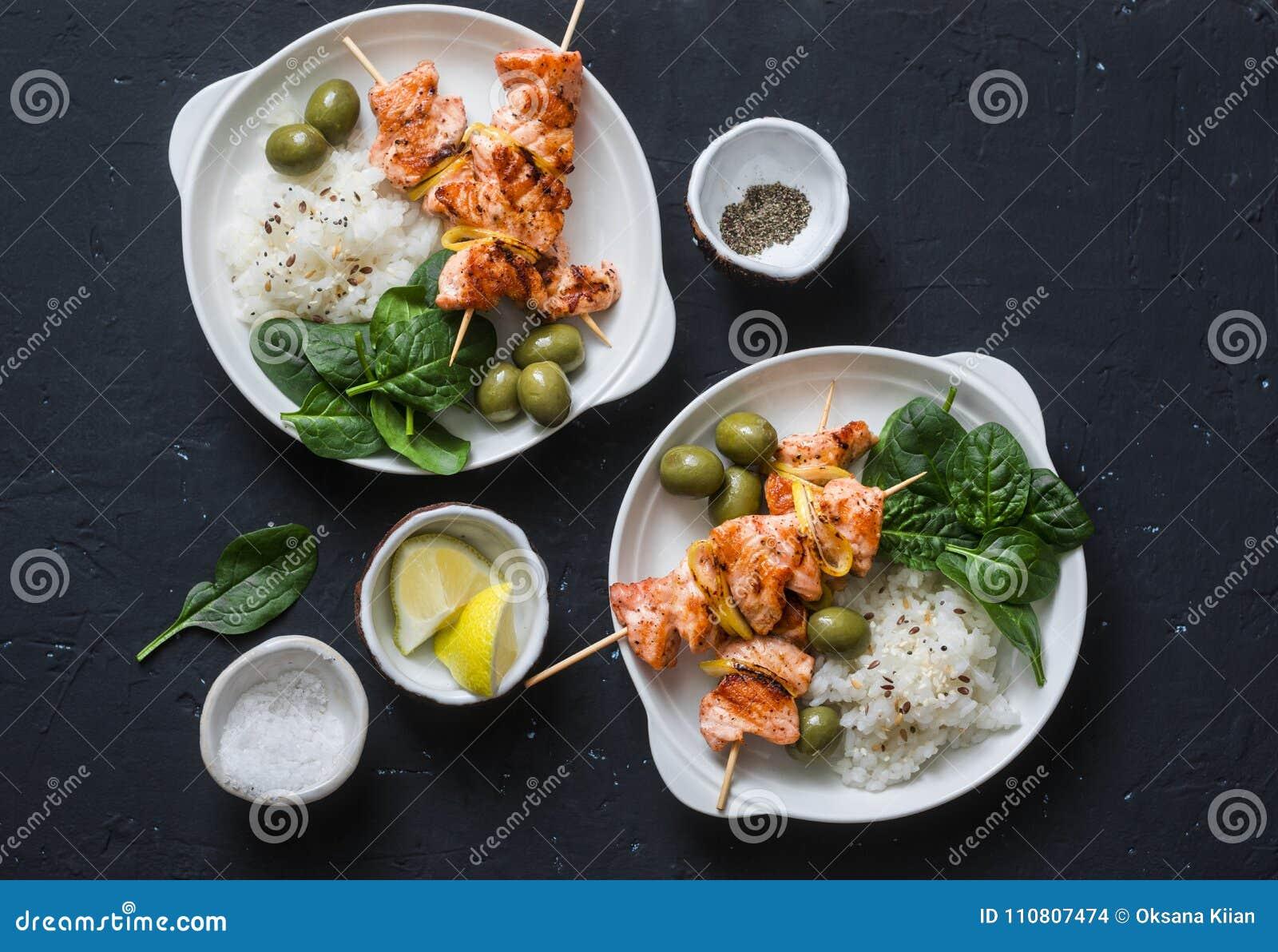 Laxsteknålar, oliv, spenat, ris - sund lunchtabell Grillad laxfisksteknål och sidomaträtt på en mörk bakgrund