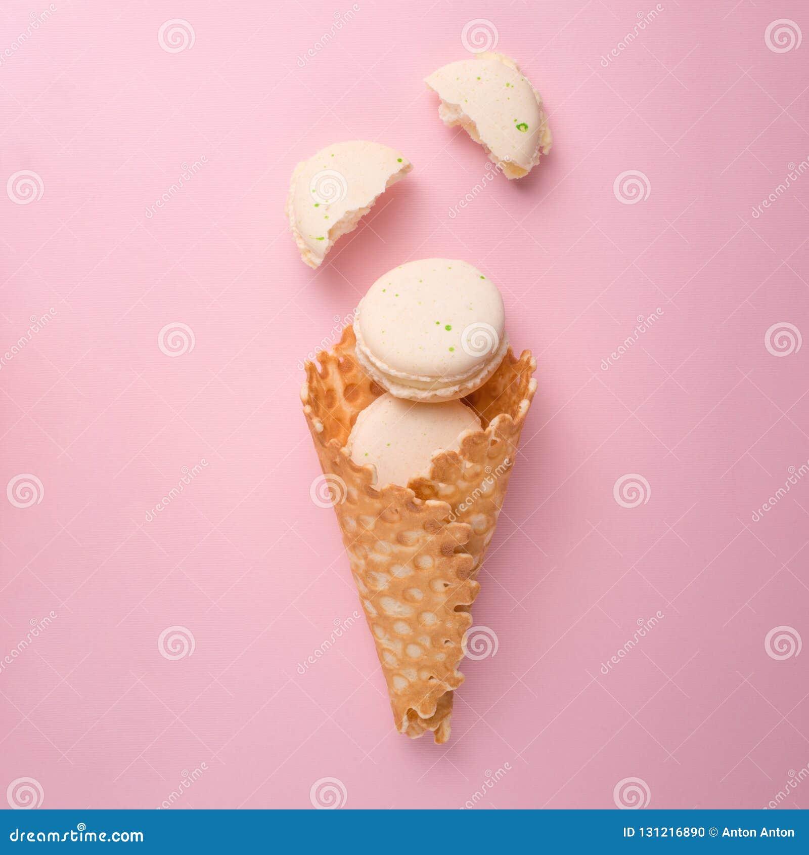 Lay cukierki rożka opłatki z białymi macaroons na pastelu świetle - różowy tło, odgórny widok Pojęcie wiosny lub lata nastrój