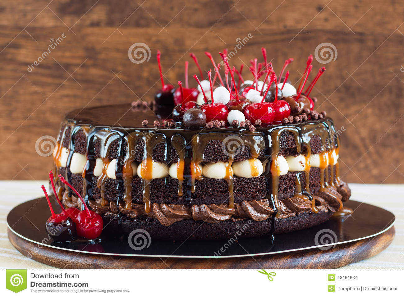 Layered chocolate cake decorated with cream, cherries and chocolate ...