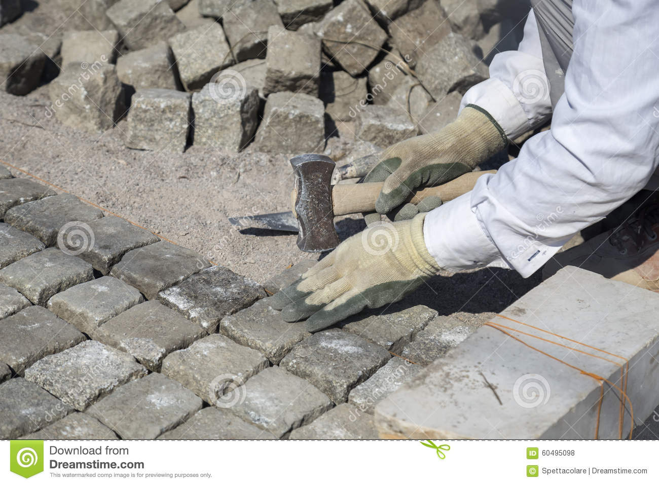 Laying Natural Stone : Laying natural granite stone cobbles in sand stock photo