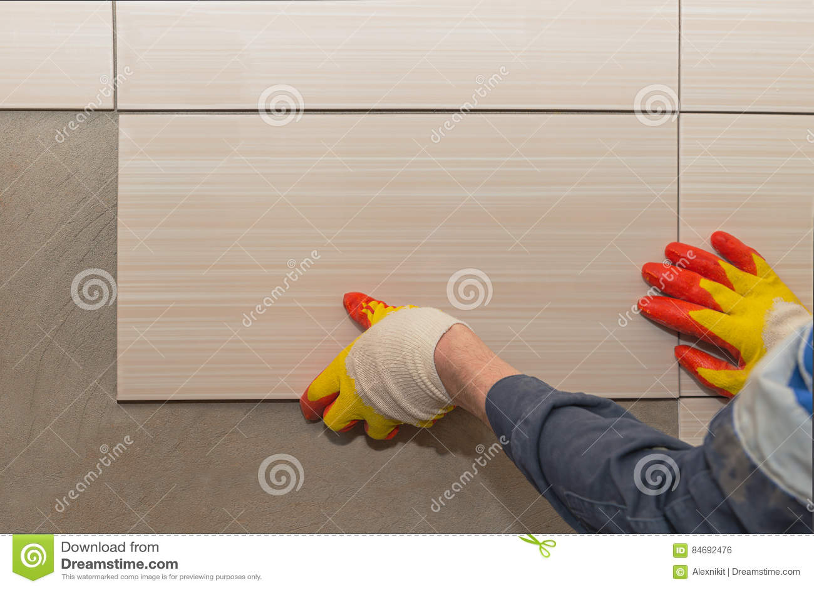 Laying tiles on the wall stock photo. Image of human - 84692476