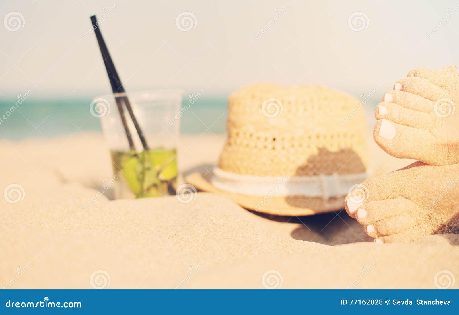Lazer no verão - bonito dos pés  sexy  das mulheres, dos pés fêmeas no Sandy Beach com chapéu e do cocktail do mojito Cocktail de
