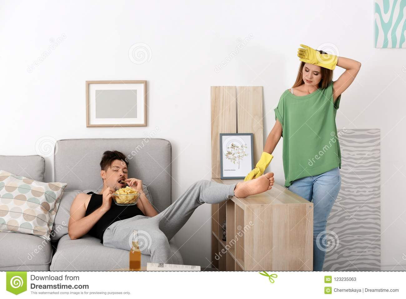 Lazy husband lying on sofa and his wife cleaning