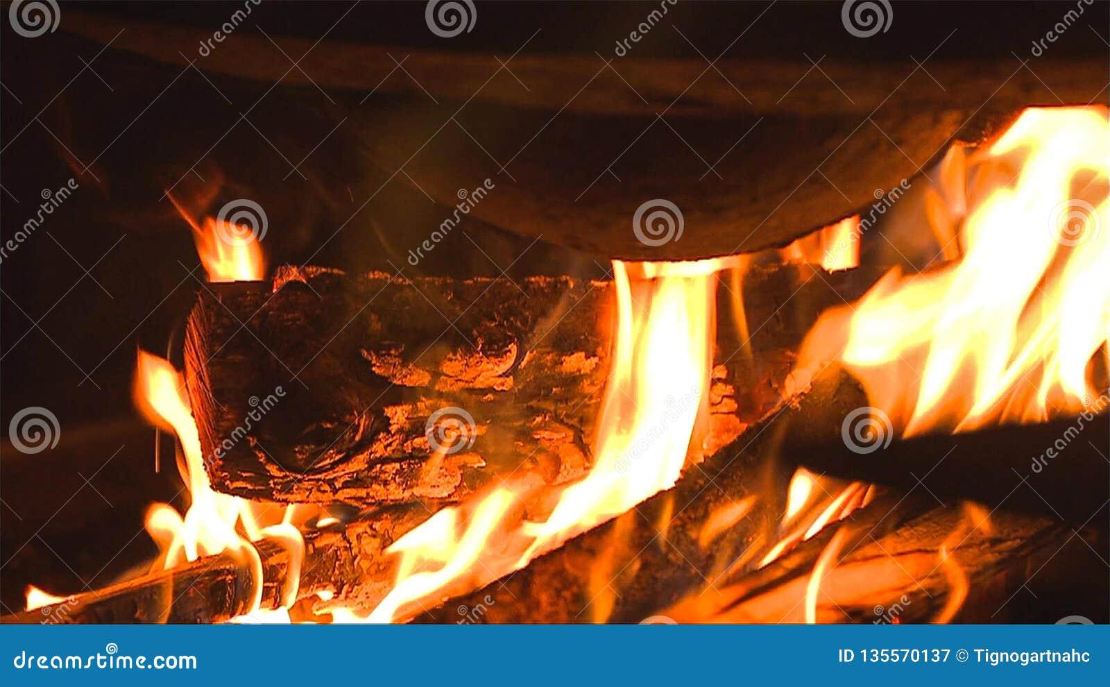 Leña ardiente en el cierre de la chimenea para arriba