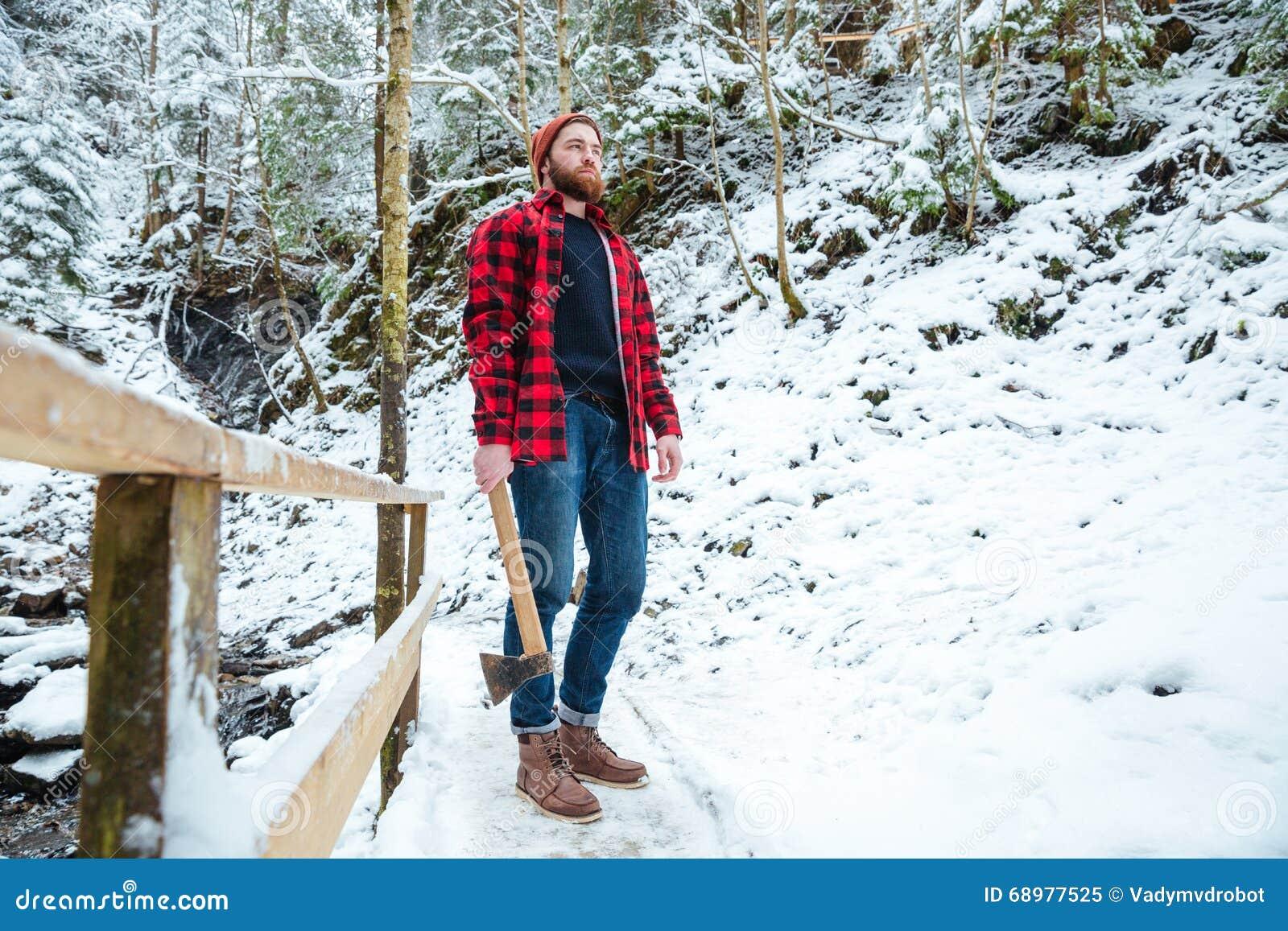 Leñador barbudo hermoso que sostiene el hacha en bosque del invierno de la montaña