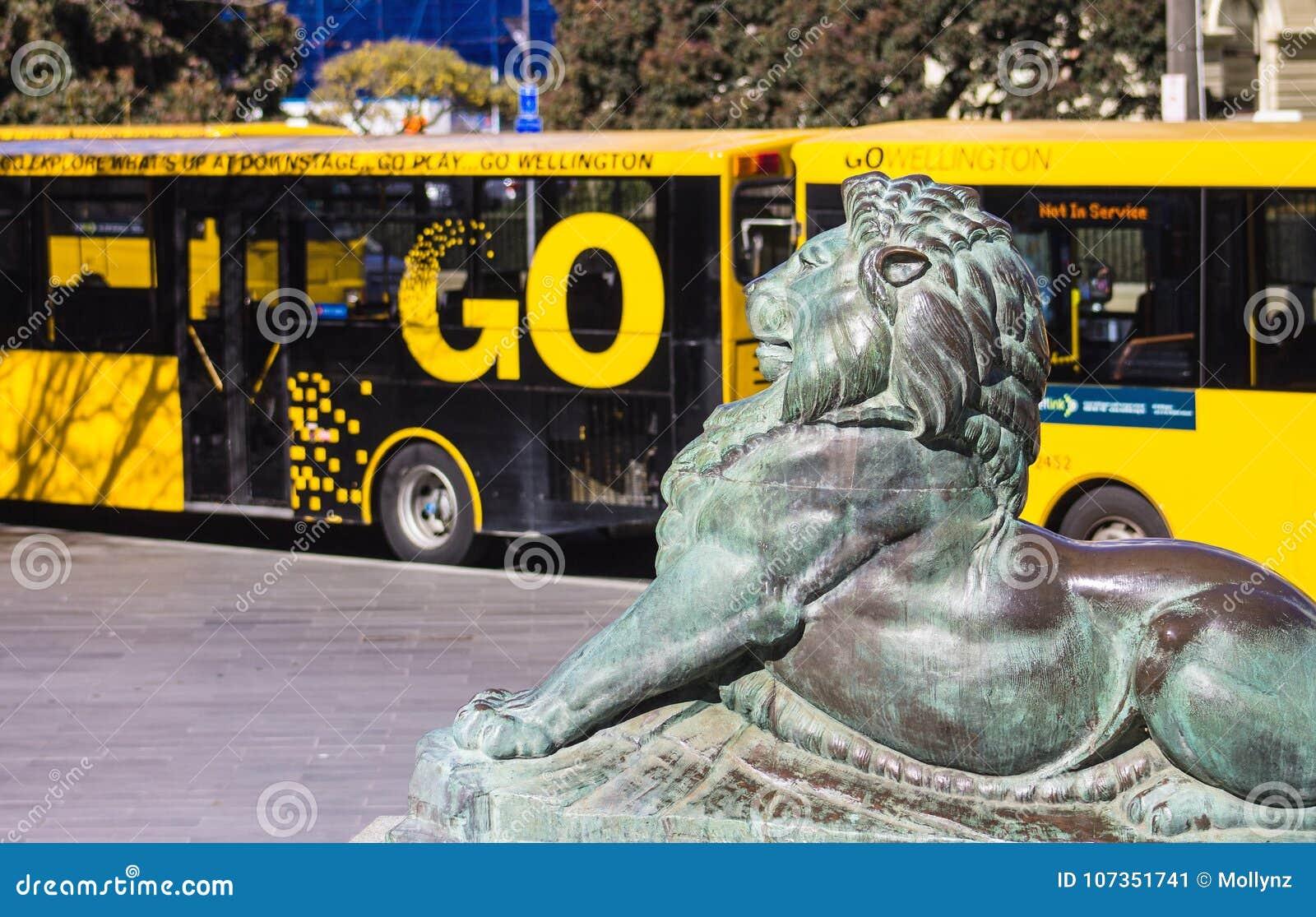León de bronce en la base de Wellington Cenotaph con los autobuses de la ciudad en el fondo