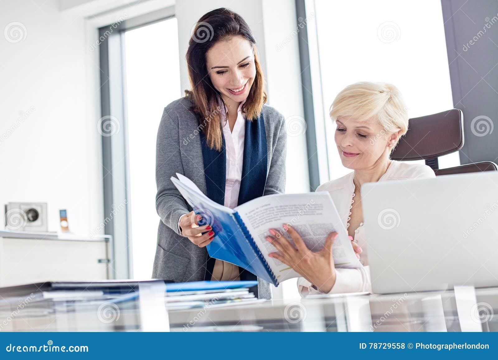 Le affärskvinnaläseboken på skrivbordet i regeringsställning