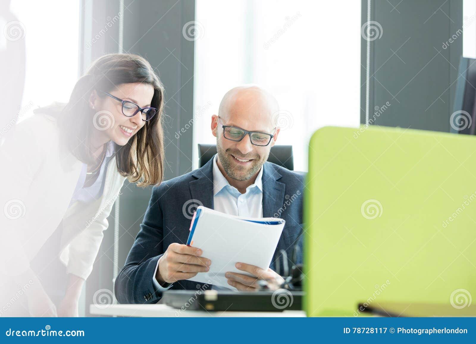 Le affärskvinnan och affärsmanläseboken på kontoret