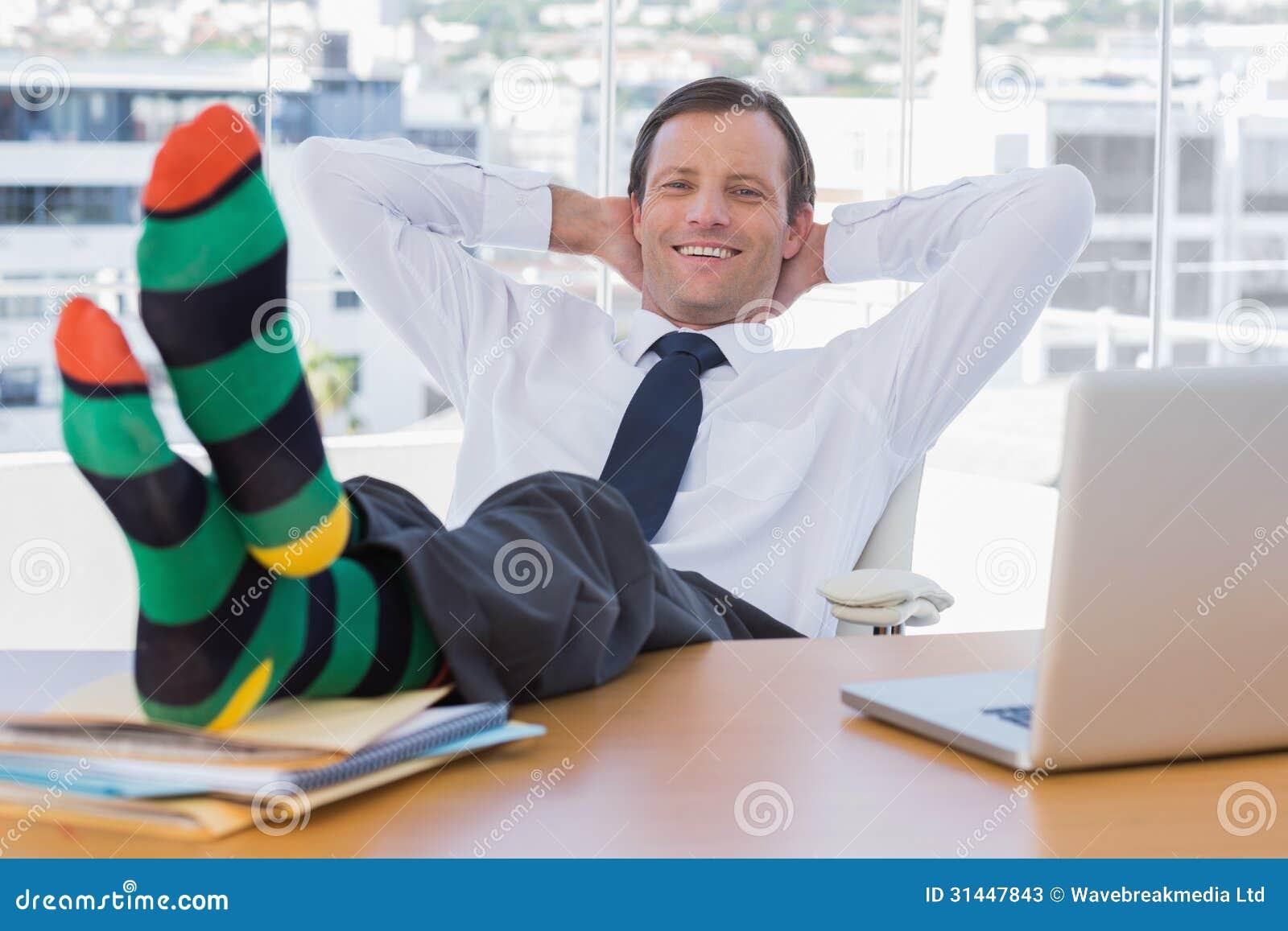 Le affärsmannen som kopplar av med fot på hans skrivbord