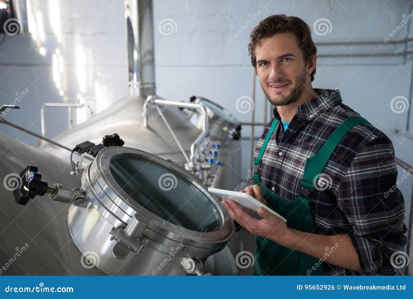 Le arbetaren som använder den digitala minnestavlan på fabriken