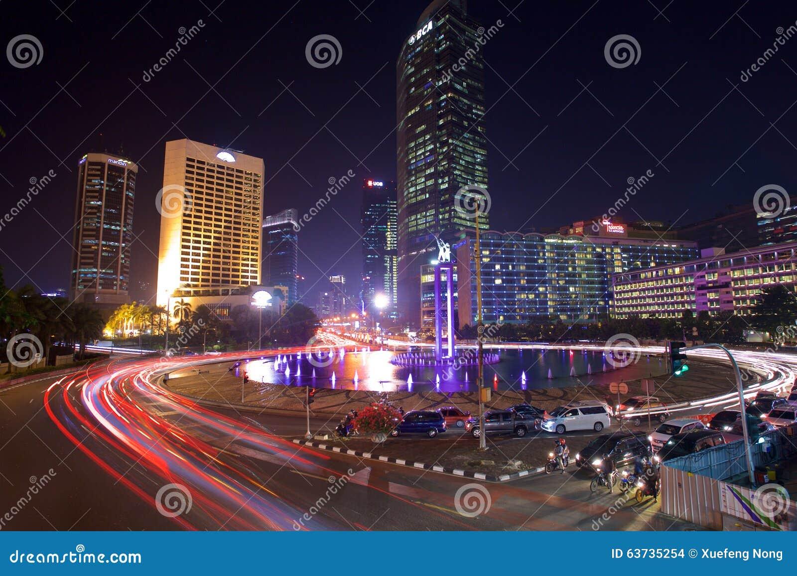 Le automobili ed i bus si precipitano attraverso la rotonda dell Indonesia della plaza nel distretto aziendale di Jakarta