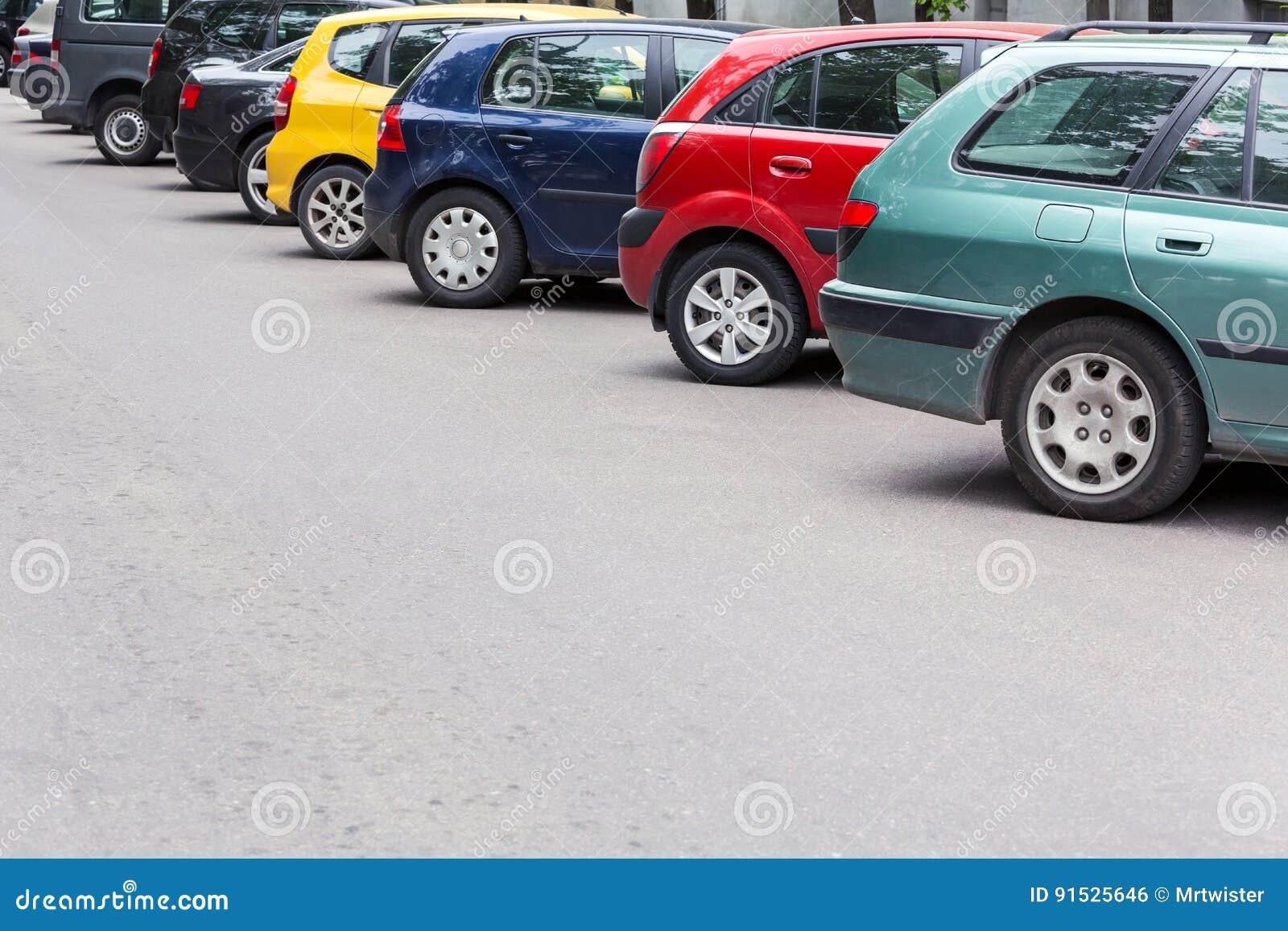 Le automobili multicolori hanno parcheggiato diagonalmente al parcheggio nella via