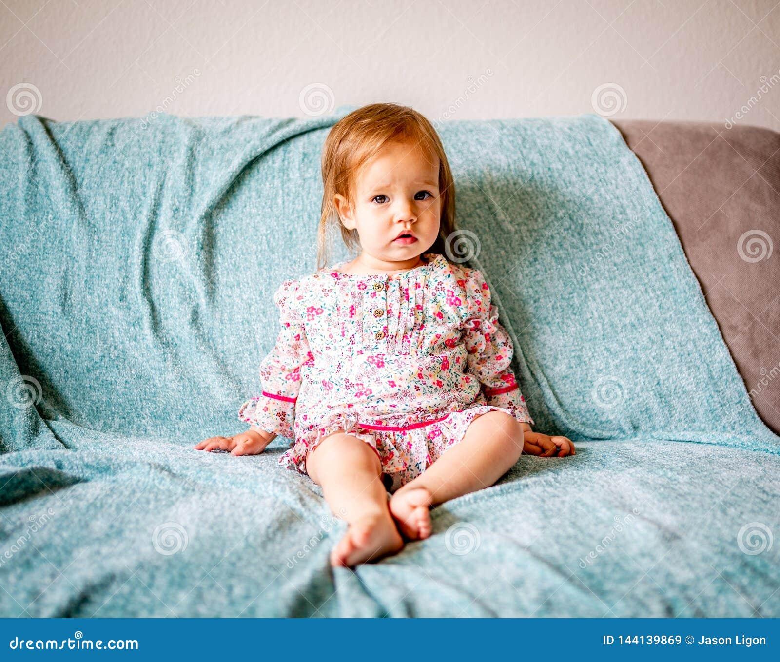 Le bébé adorable s assied sur le divan
