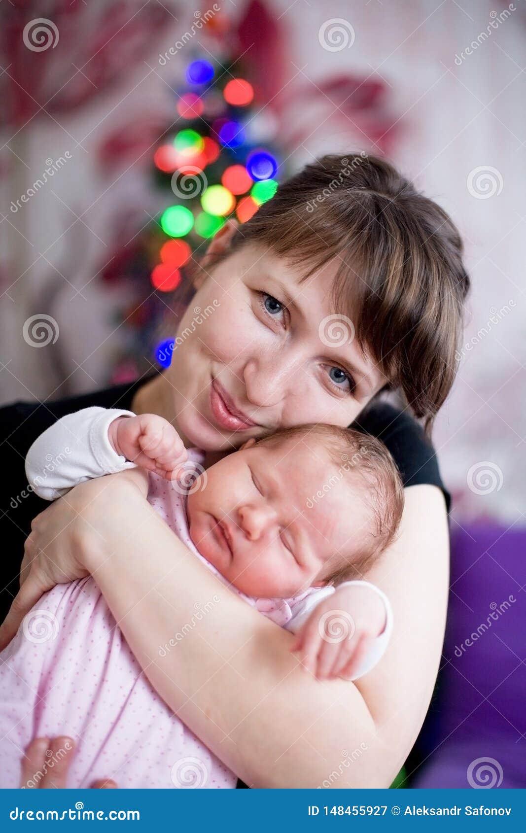 Le bébé dort dans les bras de la femme de mère