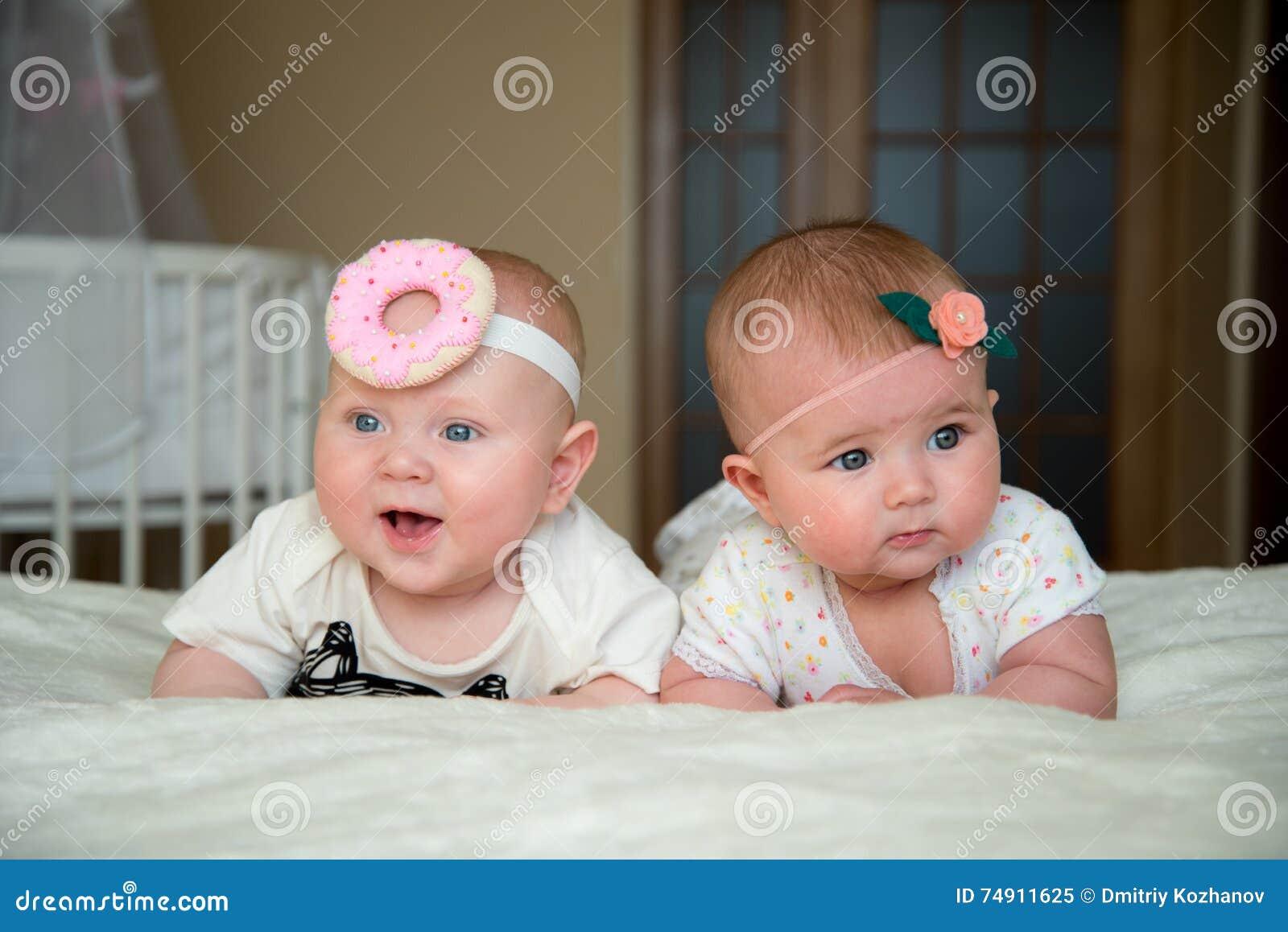 Le bébé garçon et la fille jumeaux se trouvent sur le lit