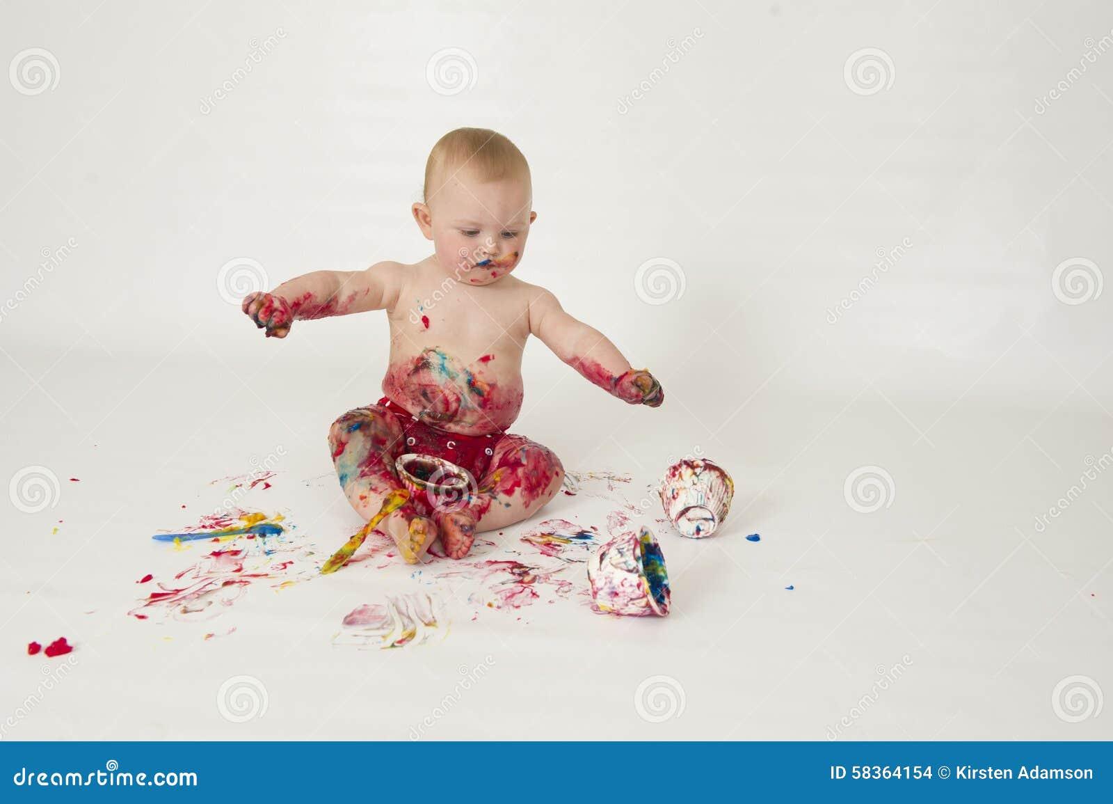 Le bébé garçon jouant avec fait maison fingerpaints