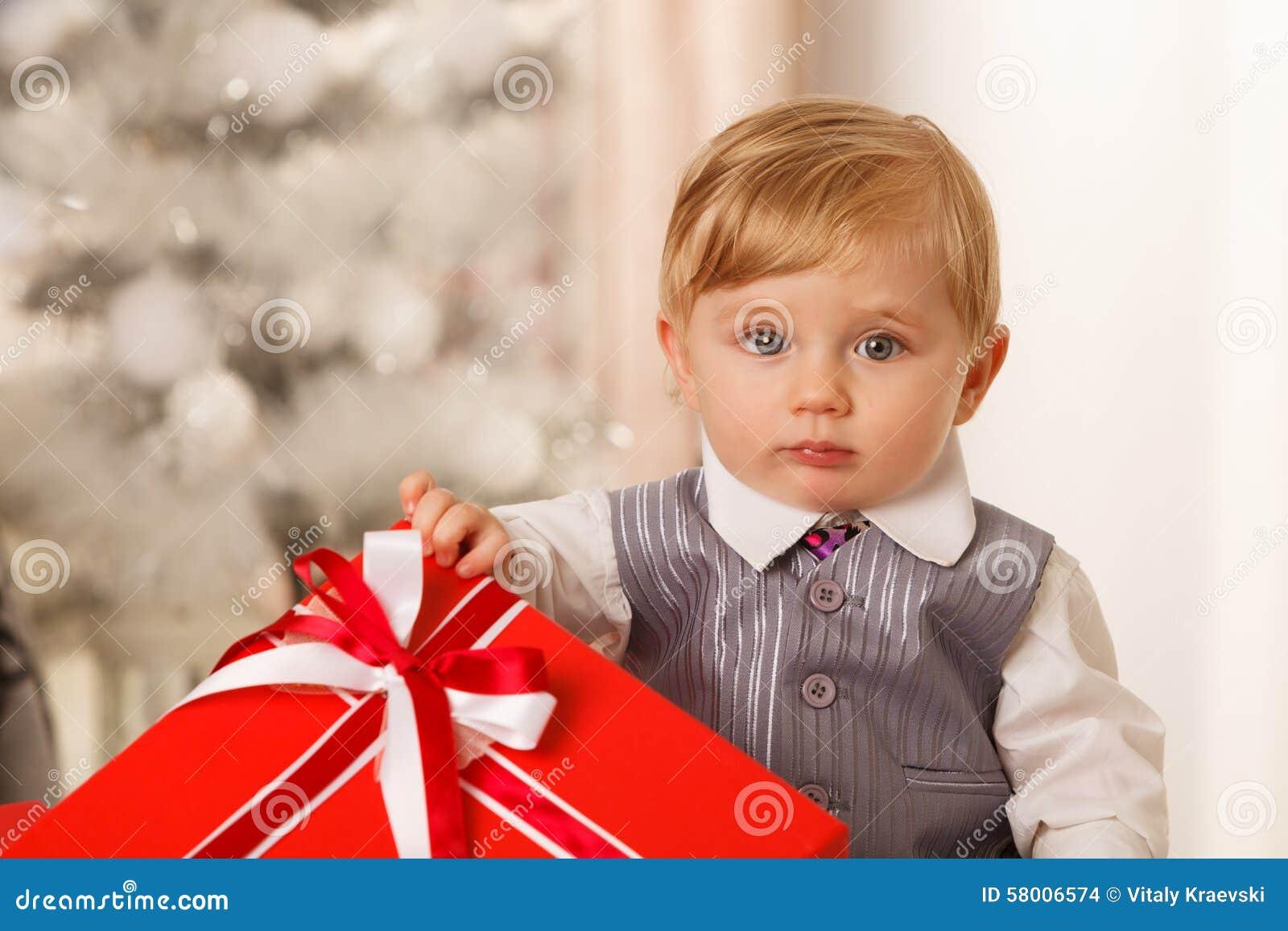 Le bébé garçon tient un grand boîte-cadeau rouge