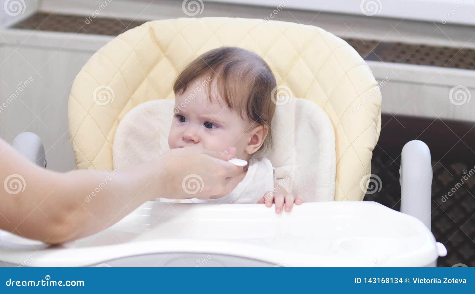 Le bébé mange du gruau de la cuillère, crache et sourit se reposant sur le highchair dans la cuisine