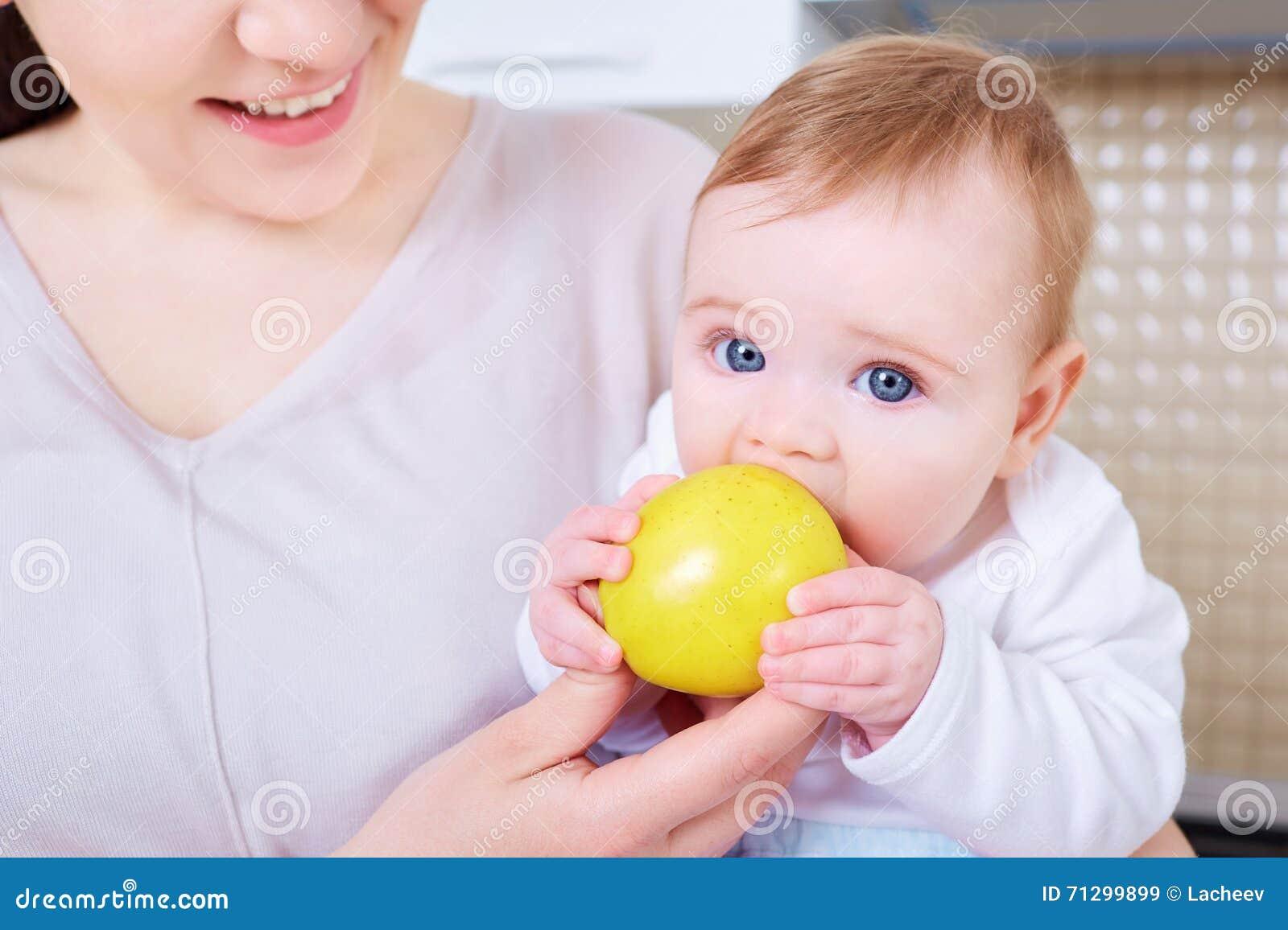 Le bébé mange la pomme jaune Enfant