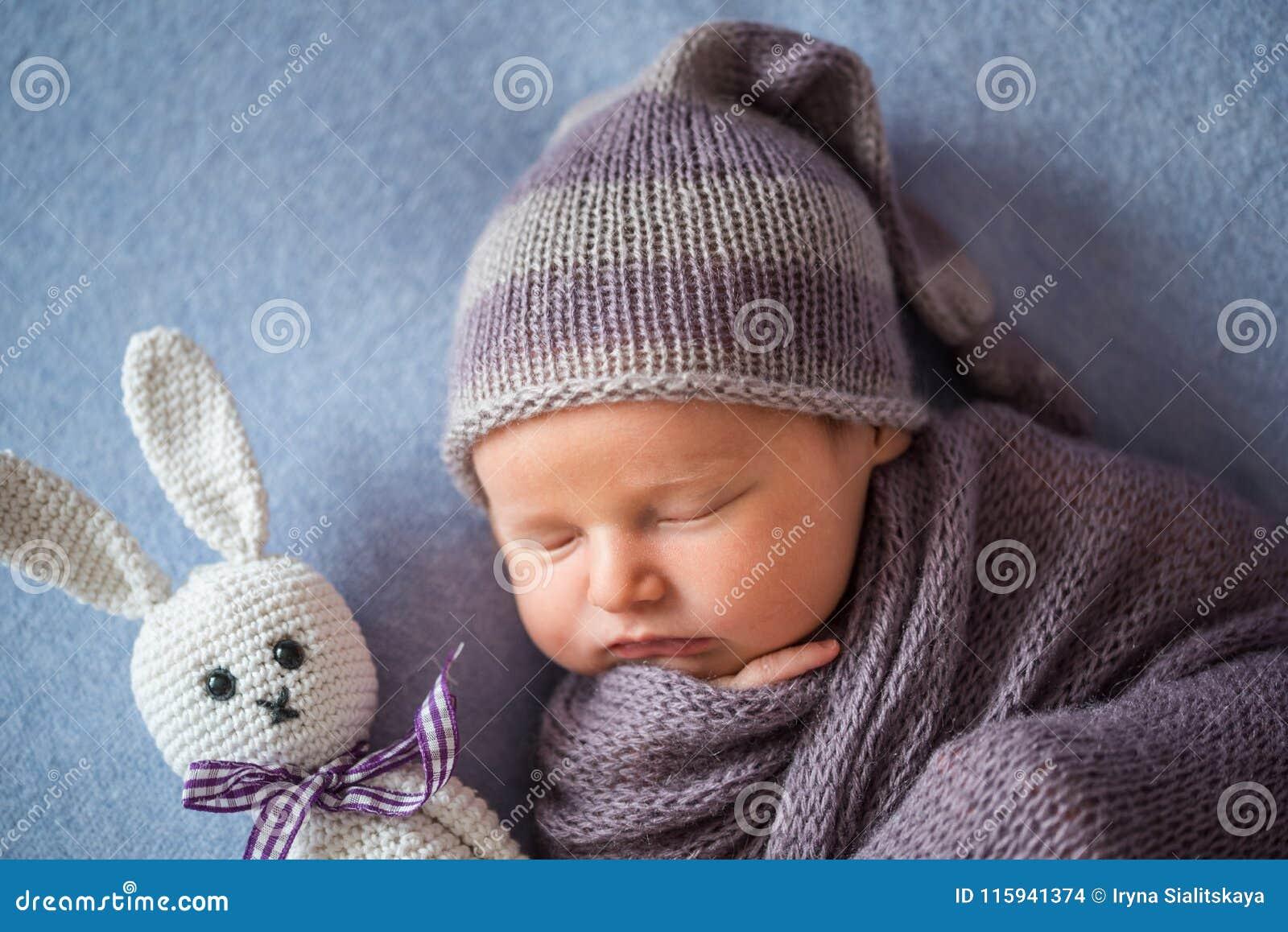Le bébé nouveau-né de sommeil minuscule couvert de pourpre riche a coloré l enveloppe