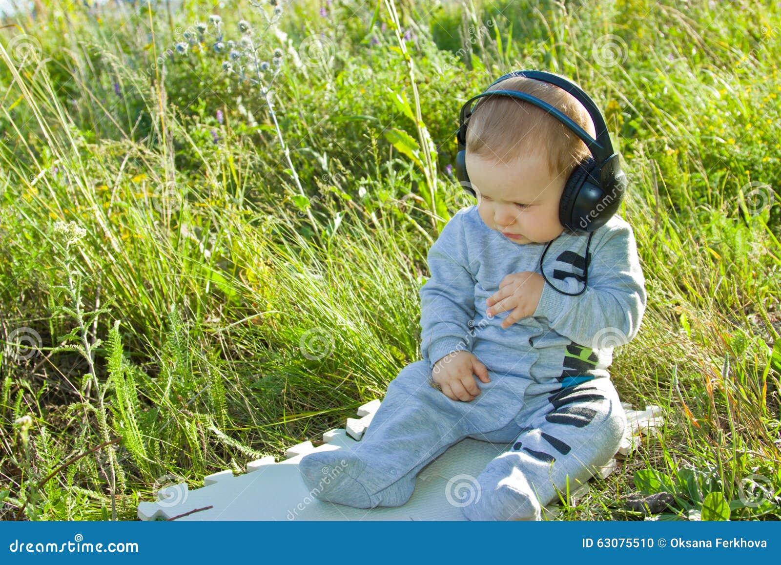 Download Le Bébé S'assied Sur Un Pré Avec Des écouteurs Photo stock - Image du casque, entendez: 63075510