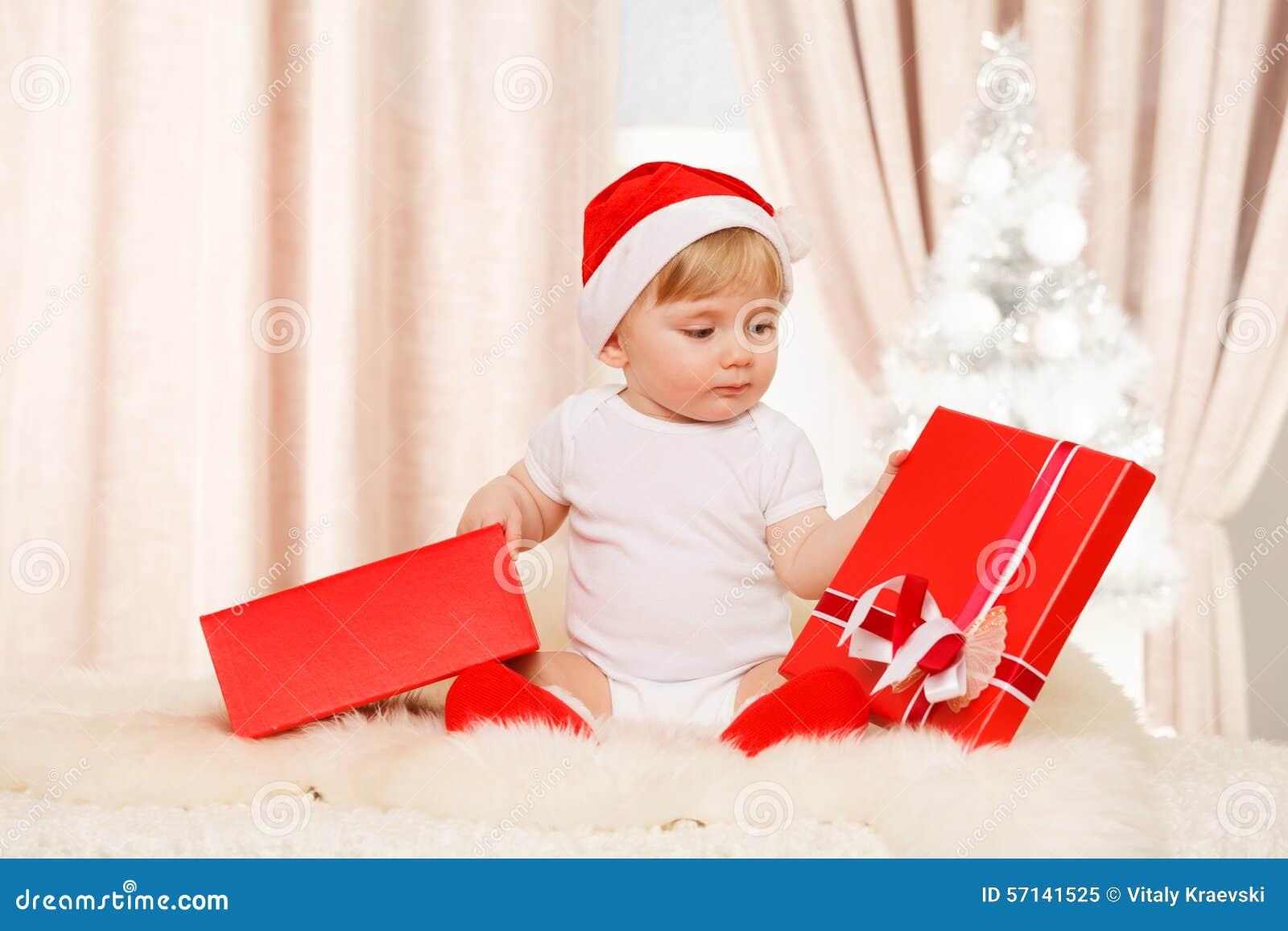 Le bébé Santa tient un grand boîte-cadeau rouge