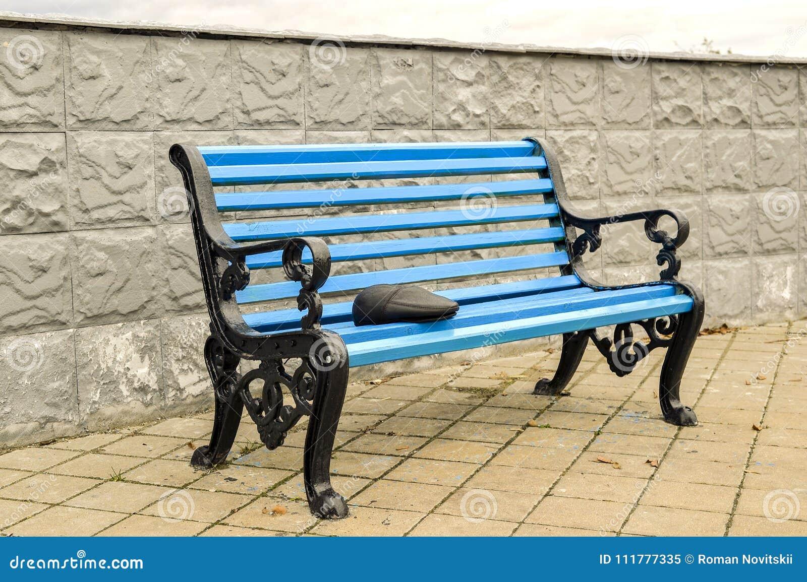 Le banc bleu en parc sur le trottoir carrelé aucun corps