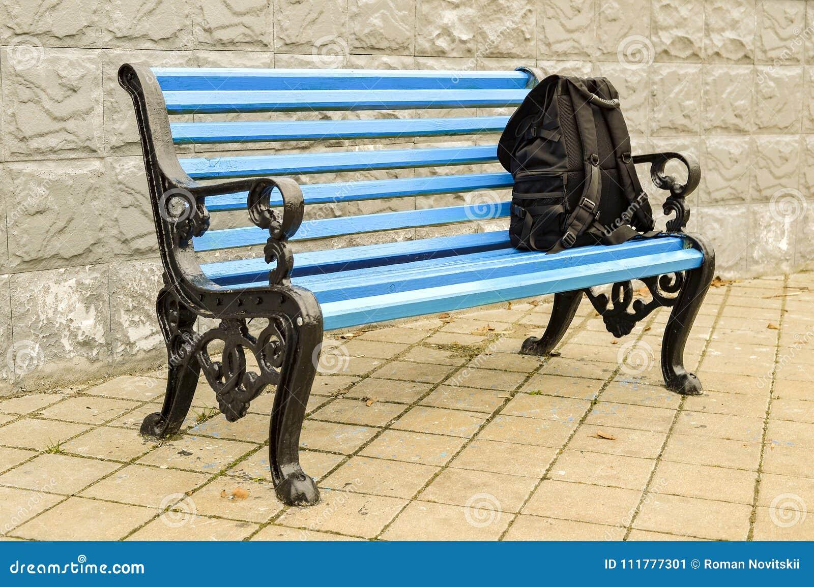 Le banc bleu en parc sur le trottoir carrelé avec un sac à dos noir aucun corps