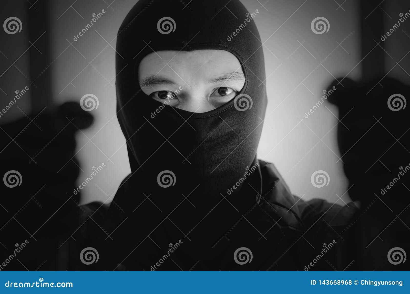 Le bandit portant un masque est prisonnier agité en prison tenant des barres sur le fond blanc