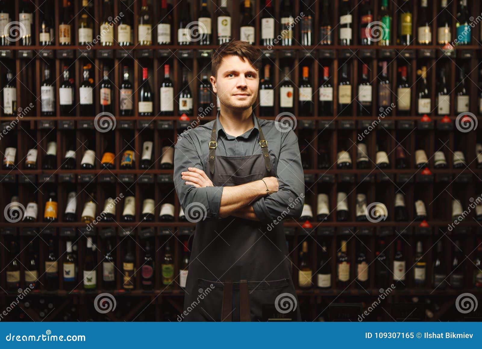 Le Barkeeper se tient dans la cave avec des étagères pleines des bouteilles