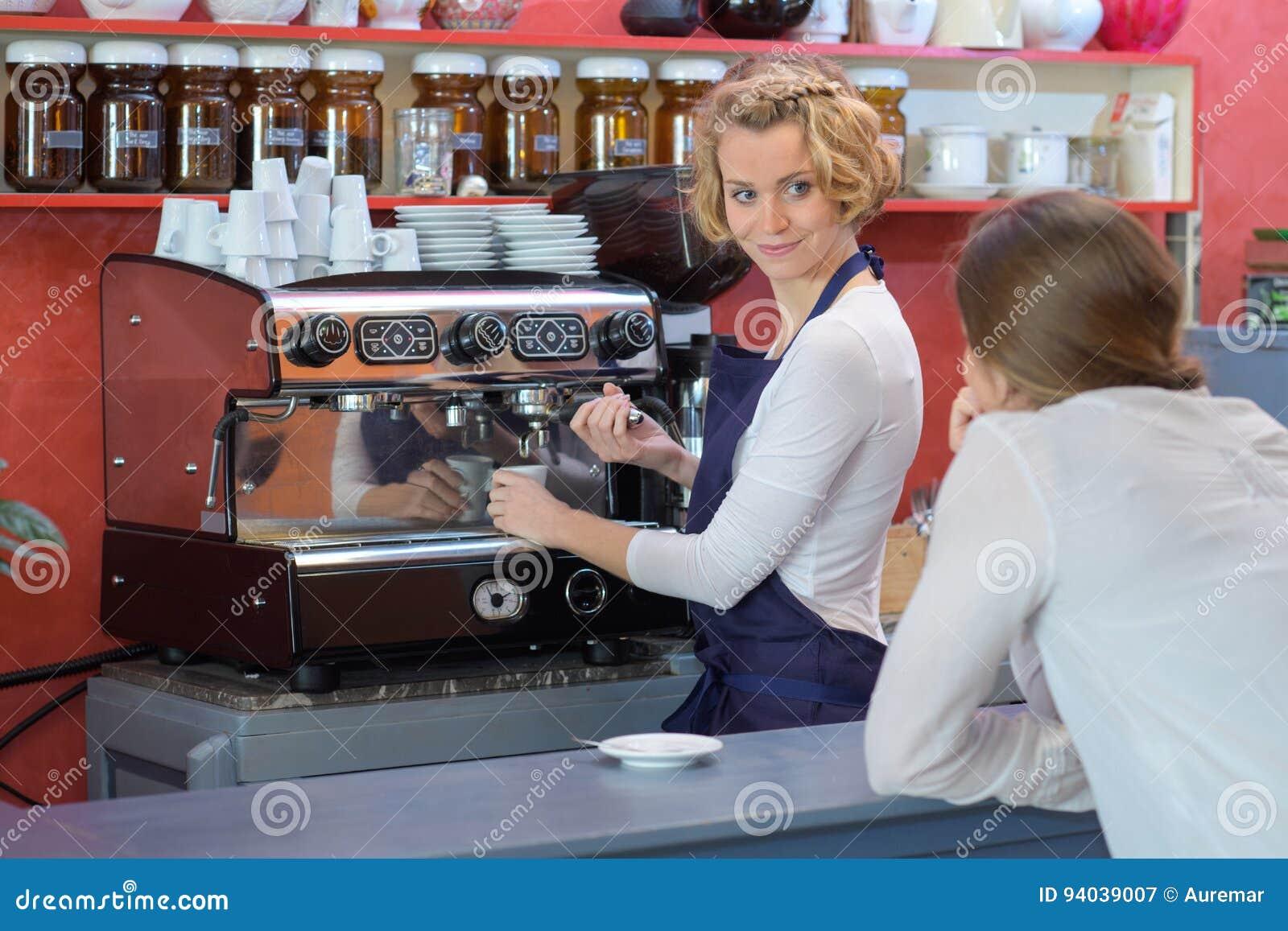 Le barman féminin fait le café à la barre