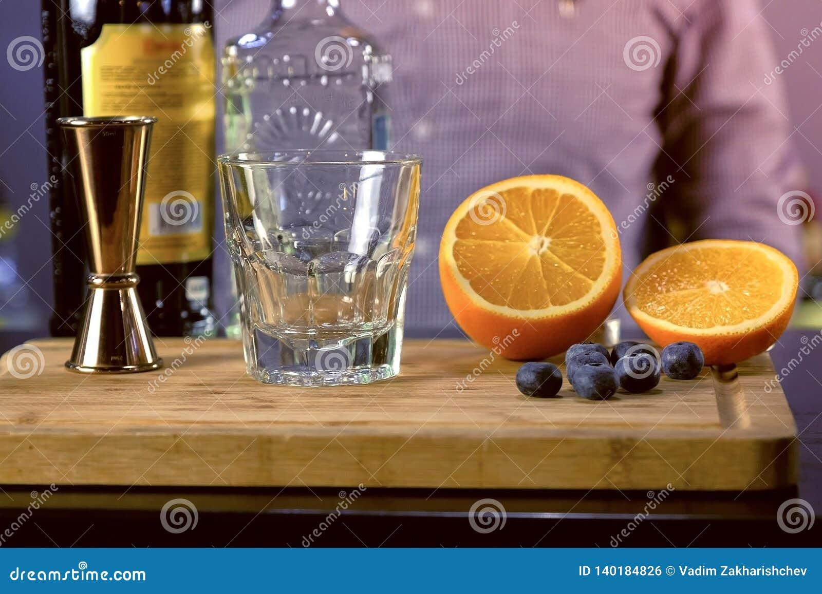 Le barman prépare les ingrédients pour le cocktail d alcool avec la tequila, l angustura amer et les fruits Remet le plan rapproc