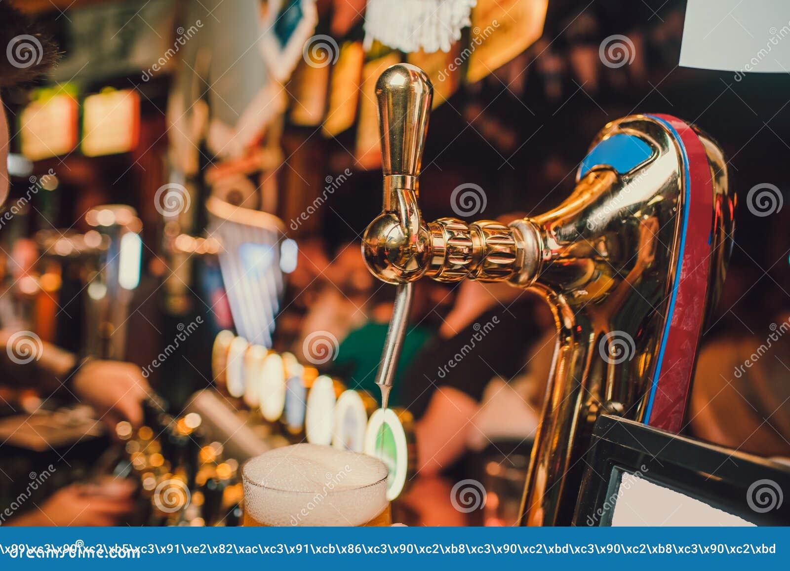 Le barman remet verser une bière blonde dans un verre