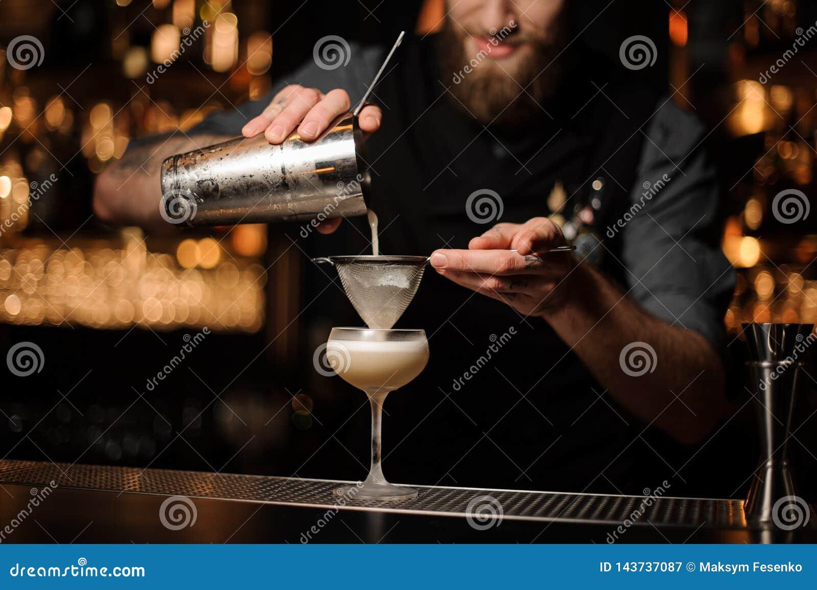 Le barman verse le cocktail ajoutant le mélange aigre en verre