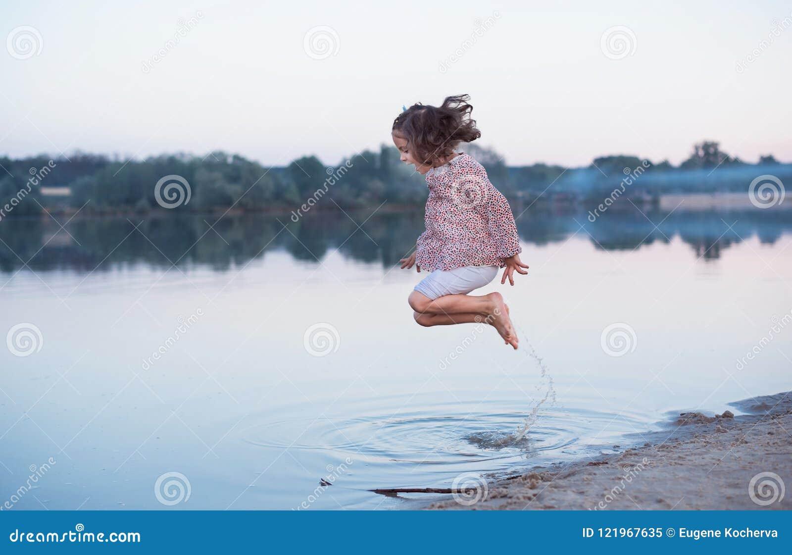 Le beau bébé avec les cheveux bouclés saute gaiement sur la banque du lac Promenade active de ressort en plein air