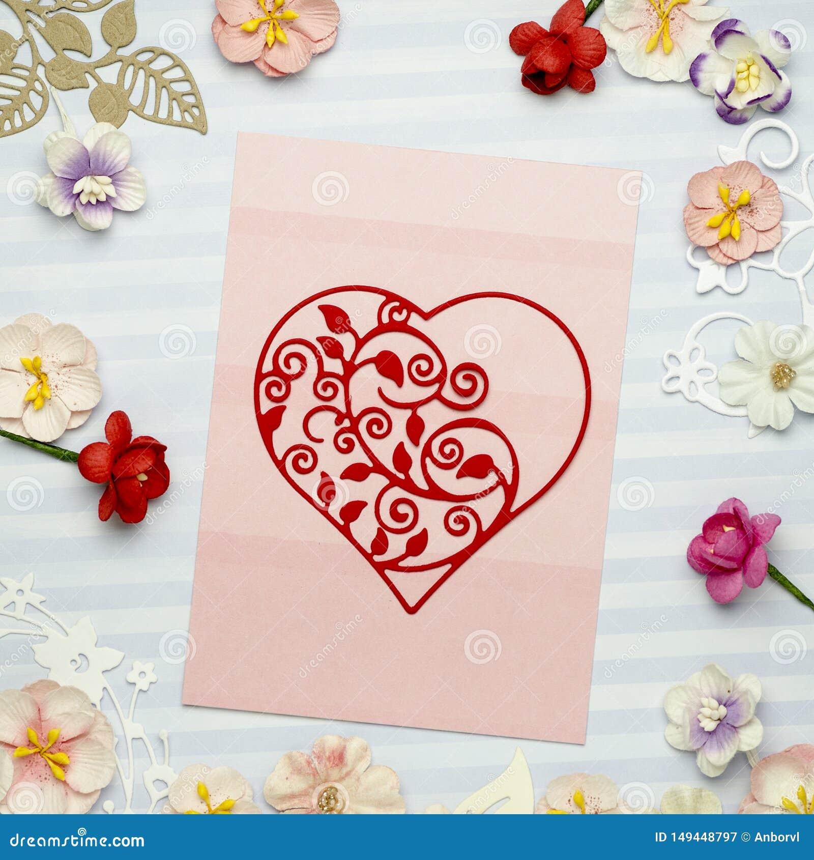 Le beau coeur a fait du papier sur une carte rose, entour? par les fleurs de papier color?es