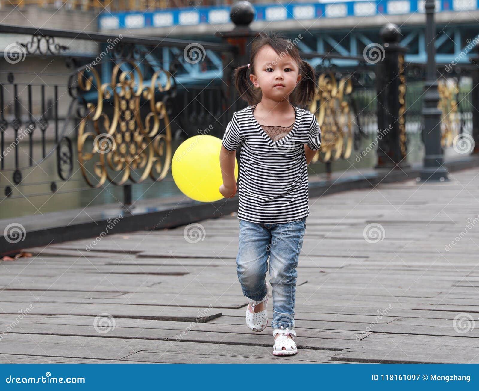 Le beau jeu adorable vilain mignon chinois asiatique de fille avec le ballon et ont l amusement extérieur dans la promenade heure