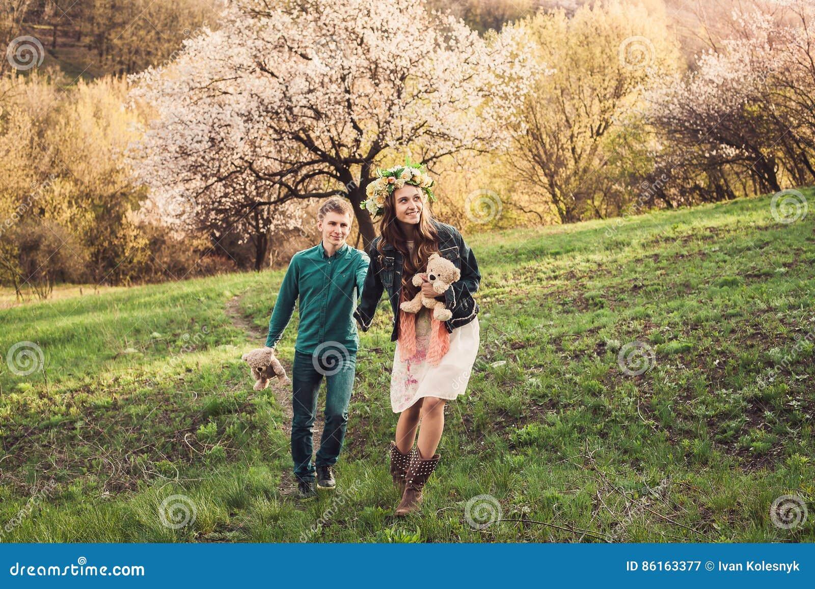 Le beau jeune couple fonctionne sur le chemin dans le for Fleurs dans le jardin