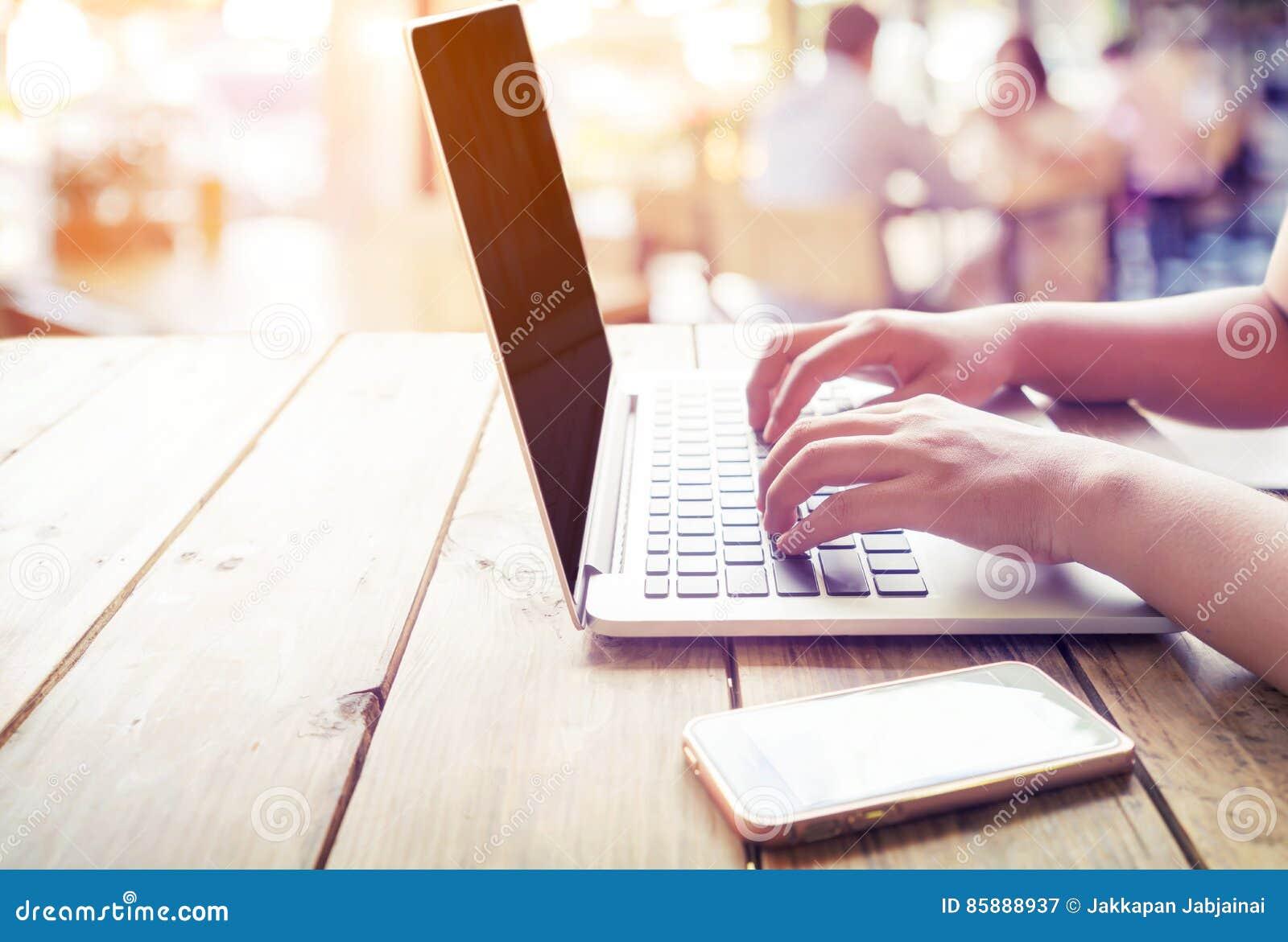 Le beau jeune ` indépendant s de femme remet travailler occupé sur son ordinateur portable se reposant à la table en bois dans un