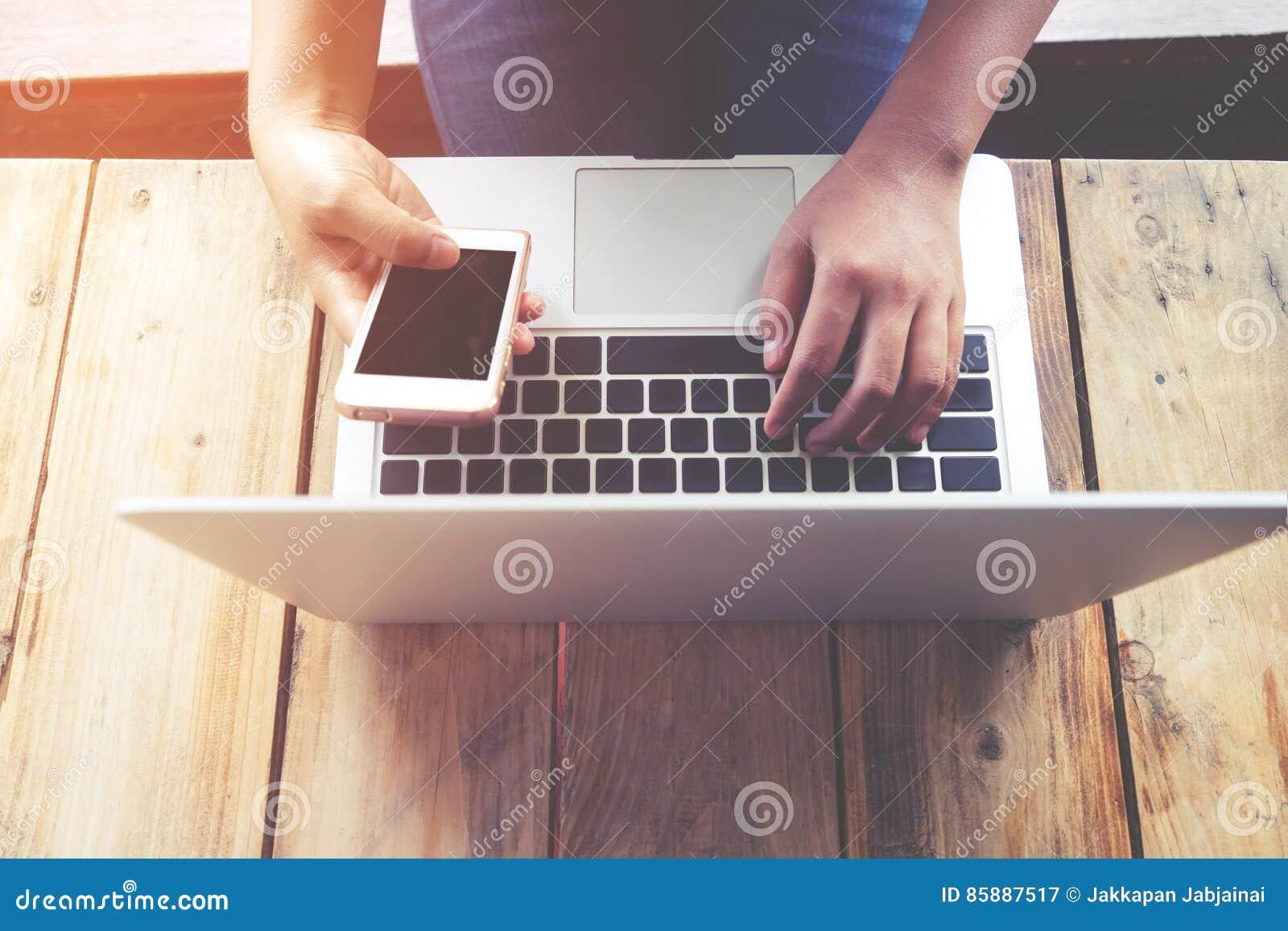 Le beau jeune ` s de femme de hippie remet travailler occupé sur son ordinateur portable, femelle utilisant le téléphone de cellu
