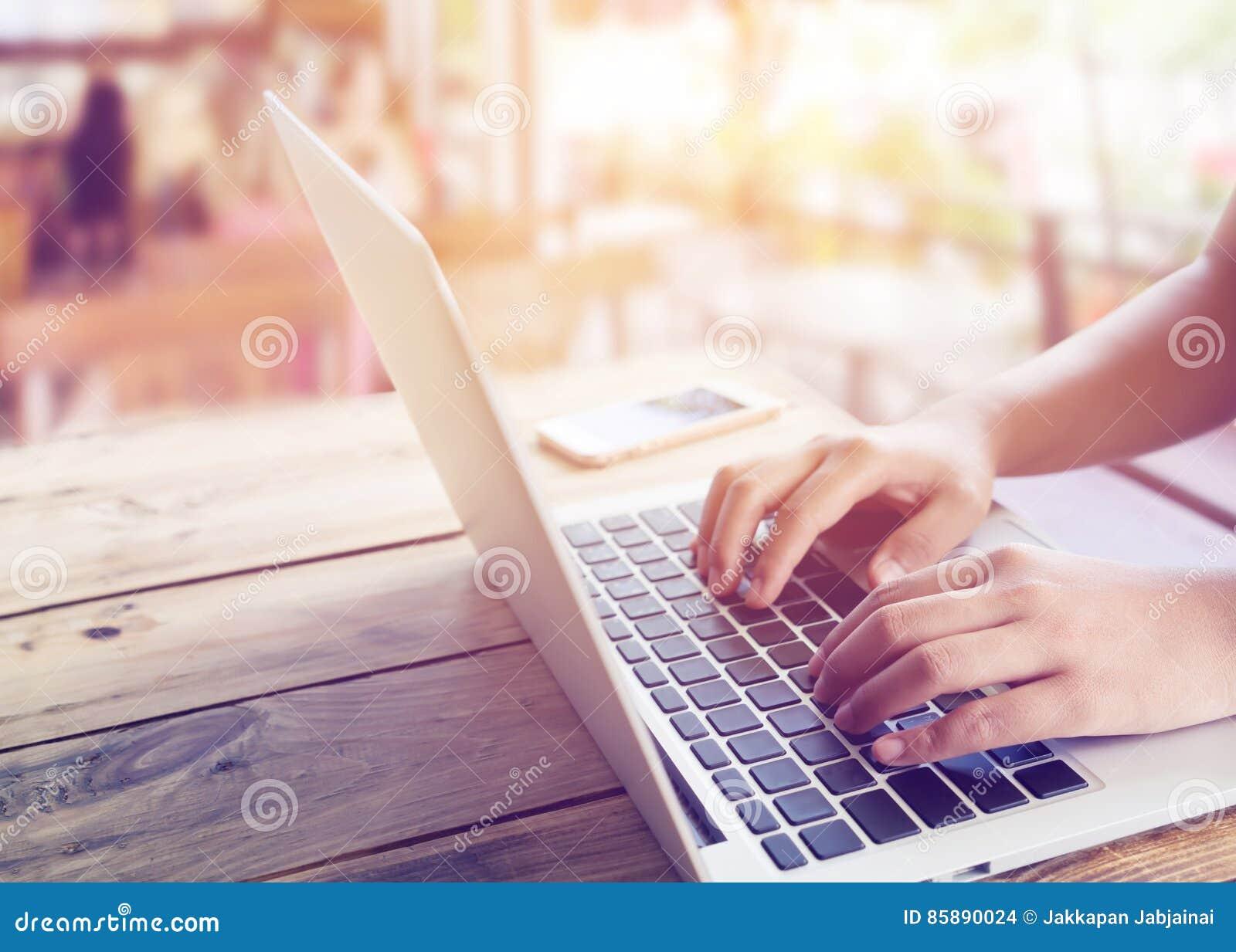Le beau jeune ` s de femme de hippie remet travailler occupé sur son ordinateur portable se reposant à la table en bois dans un c